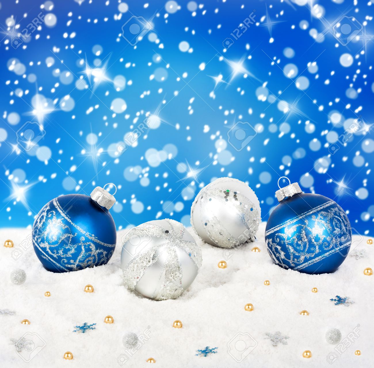 Blue and silver Christmas balls on snow background with stars